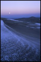 Dunes at dawn with snow and moon. Great Sand Dunes National Park, Colorado, USA.