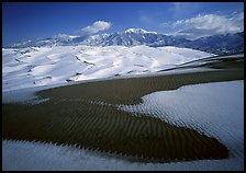 Patch of sand, snow-covered dunes, Sangre de Christo mountains. Great Sand Dunes National Park and Preserve, Colorado, USA.