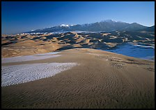 Sand dunes with snow patches and Sangre de Christo range. Great Sand Dunes National Park, Colorado, USA.