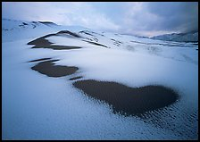 Patches of uncovered sand in snow-covered dunes, mountains, and dark clouds. Great Sand Dunes National Park, Colorado, USA.