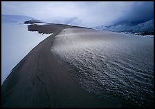 Zig-zag pattern of sand amongst Snow on the dunes. Great Sand Dunes National Park, Colorado, USA.