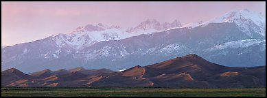 Sand dunes below snowy mountain range at sunset. Great Sand Dunes National Park and Preserve (Panoramic color)