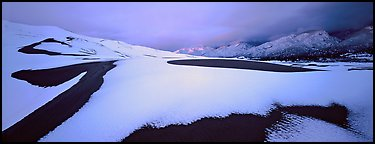 Snow-covered dune landscape and mountains at dawn. Great Sand Dunes National Park and Preserve (Panoramic color)
