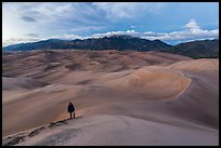 Hiker climbing high dune. Great Sand Dunes National Park, Colorado, USA. (color)