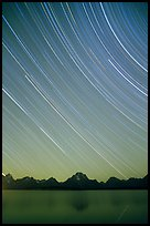 Star trails on Teton range above Jackson lake, dusk. Grand Teton National Park, Wyoming, USA.