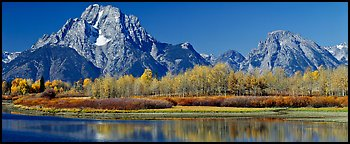 Rugged mountains rising above tree-lined lake in autumn. Grand Teton National Park (Panoramic color)