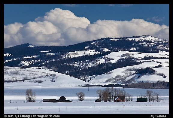 Distant row of barns, hills and clouds in winter. Grand Teton National Park, Wyoming, USA.