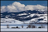 Distant row of barns, hills and clouds in winter. Grand Teton National Park, Wyoming, USA. (color)