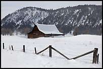 Fence and historic Moulton Barn in winter. Grand Teton National Park, Wyoming, USA.