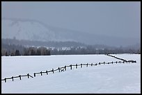 Wooden fence, snow-covered flat, hills in winter. Grand Teton National Park, Wyoming, USA.