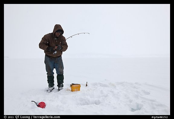 Ice fisherman standing next to hole, Jackson Lake. Grand Teton National Park (color)