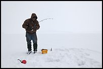 Ice fisherman standing next to hole, Jackson Lake. Grand Teton National Park, Wyoming, USA.