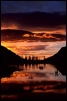 Sunrise with colorful clouds reflected on a pond in Horseshoe park. Rocky Mountain National Park, Colorado, USA.