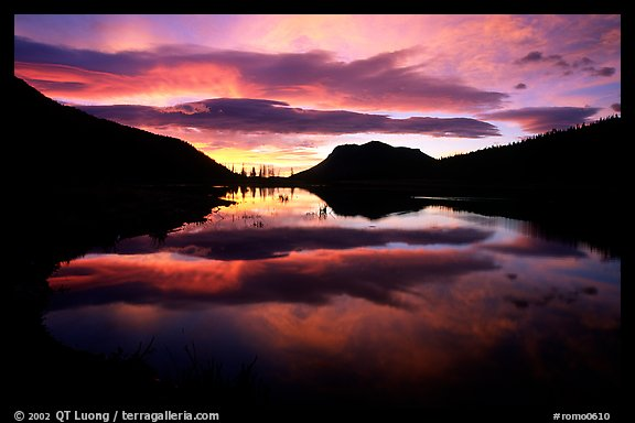 Colorful sunrise clouds reflected in a pond in Horseshoe park. Rocky Mountain National Park (color)