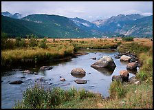 Creek, boulders, and meadow surrounded by mountains, autumn. Rocky Mountain National Park, Colorado, USA.