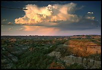 Storm cloud and badlands at sunset, South Unit. Theodore Roosevelt National Park, North Dakota, USA.