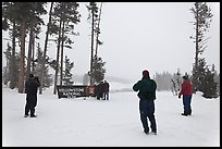 Visitors take pictures with entrance sign in winter. Yellowstone National Park, Wyoming, USA.