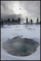Thermal pool and dark clouds, winter. Yellowstone National Park, Wyoming, USA. (color)