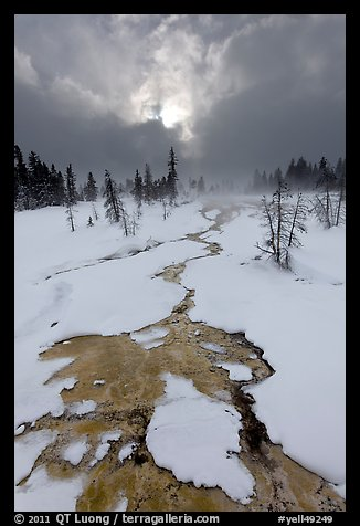 Colorful thermal stream and dark clouds, winter. Yellowstone National Park (color)