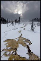 Colorful thermal stream and dark clouds, winter. Yellowstone National Park, Wyoming, USA.