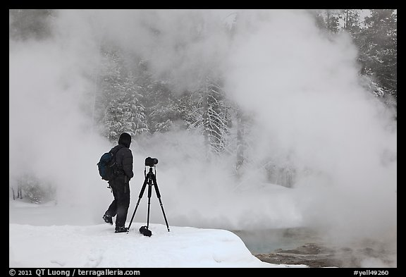 Photographer standing next to hot springs. Yellowstone National Park, Wyoming, USA.