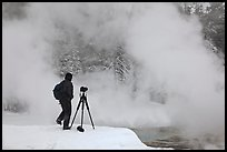 Photographer standing next to hot springs. Yellowstone National Park, Wyoming, USA. (color)