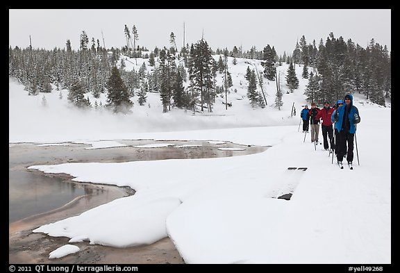 Cross country skiers pass Chromatic Spring. Yellowstone National Park, Wyoming, USA.