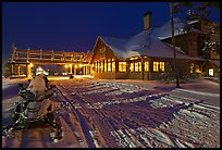 Snowmobiles parked next to Old Faithful Snow Lodge at night. Yellowstone National Park, Wyoming, USA.