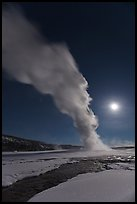 Night view of Old Faithful Geyser in winter with full moon. Yellowstone National Park, Wyoming, USA.