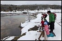 Family looks at thermal pool in winter. Yellowstone National Park, Wyoming, USA. (color)