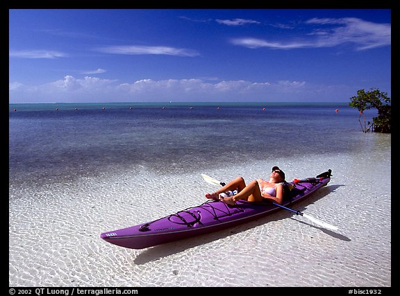 Woman reclining in kayak on shallow waters,  Elliott Key. Biscayne National Park, Florida, USA.