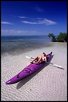 Woman sunning herself on sea kayak parked on shore,  Elliott Key. Biscayne National Park, Florida, USA.