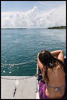 Woman relaxes on snorkeling boat as it enters Caesar Creek. Biscayne National Park, Florida, USA. (color)