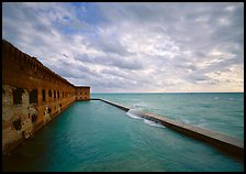 Fort Jefferson brick rampart and moat with wave over seawall, cloudy weather. Dry Tortugas National Park, Florida, USA.