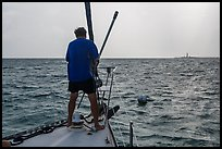 Sailor getting ready to hook mooring buoy near Loggerhead Key. Dry Tortugas National Park, Florida, USA. (color)
