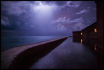 Fort Jefferson seawall at night with sky lit by thunderstorm. Dry Tortugas National Park ( color)