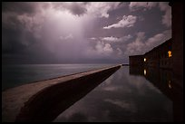 Fort Jefferson seawall at night with sky lit by tropical storm. Dry Tortugas National Park ( color)