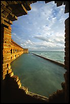 Fort Jefferson seawall and moat, framed by a crumpling embrasures, late afternoon. Dry Tortugas National Park, Florida, USA. (color)
