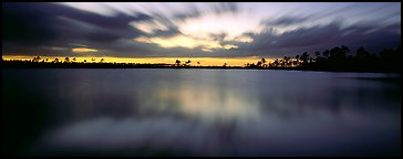 Dark clouds in motion at sunset over lake. Everglades  National Park (Panoramic color)
