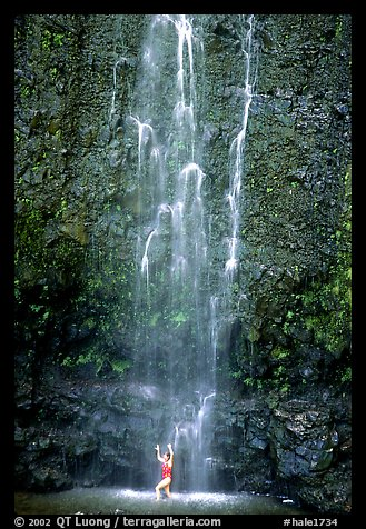 Visitor refreshes herself at the base of Waimoku Falls. Haleakala National Park, Hawaii, USA.