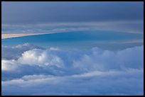 Mauna Loa between clouds, seen from Halekala summit. Haleakala National Park, Hawaii, USA.