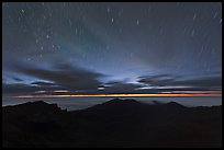 Crater ridge and stars in motion at night. Haleakala National Park, Hawaii, USA.