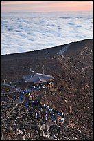 People gather to watch sunrise above sea of clouds. Haleakala National Park, Hawaii, USA.