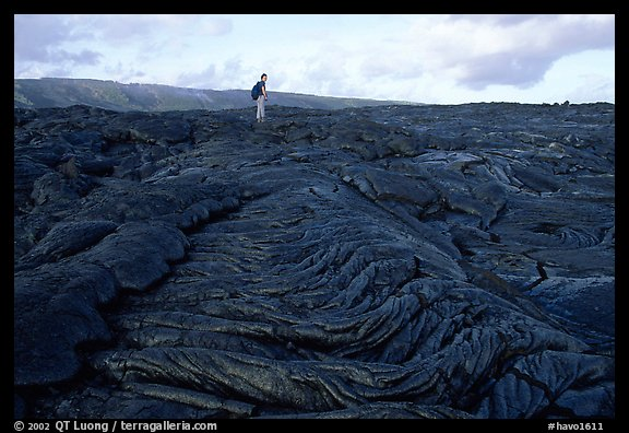 Hiker on hardened lava flow at the end of Chain of Craters road. Hawaii Volcanoes National Park, Hawaii, USA.