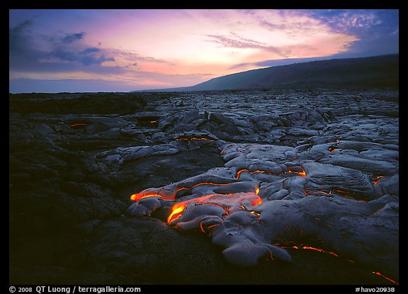 Volcanic landscape with molten lava flow and red spots at sunset. Hawaii Volcanoes National Park, Hawaii, USA.