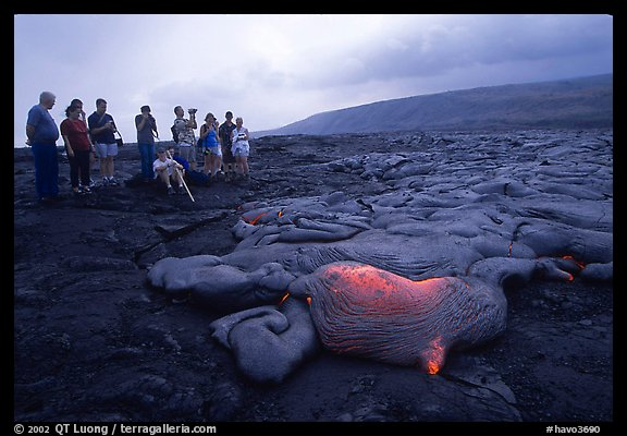 Hikers observe a live lava flow at close distance. Hawaii Volcanoes National Park (color)