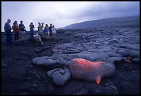 Hikers observe a live lava flow at close distance. Hawaii Volcanoes National Park, Hawaii, USA. (color)