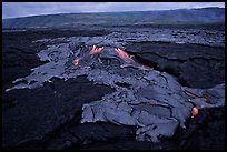 Live hot lava flows over hardened lava. Hawaii Volcanoes National Park, Hawaii, USA.