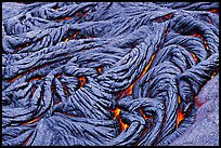Braids of pahoehoe lava with red hot lava showing through cracks. Hawaii Volcanoes National Park, Hawaii, USA.
