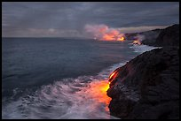Streams of hot lava flow into the Pacific Ocean at the shore of erupting Kilauea volcano. Hawaii Volcanoes National Park, Hawaii, USA. (color)